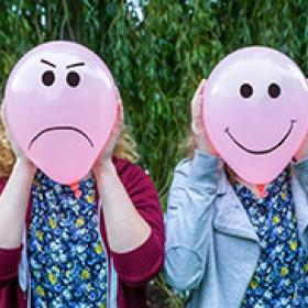 Two teenage girls holding balloons with facial expressions outdoors
