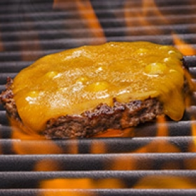 Cheeseburger cooking on a flaming grill