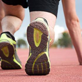Photo of a runner crouching at the starting line of a track