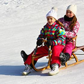 Photo of two young girls sledding
