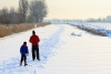 Two ice skaters glide along a frozen river